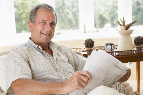 Man in living room reading newspaper smiling 500×333