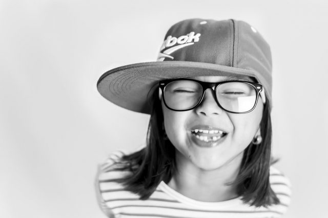 Little girl laughing, wearing hat and glasses