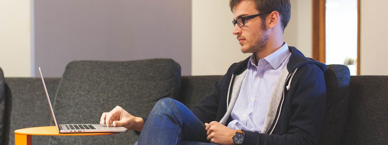 Man wearing eyeglasses, working on computer