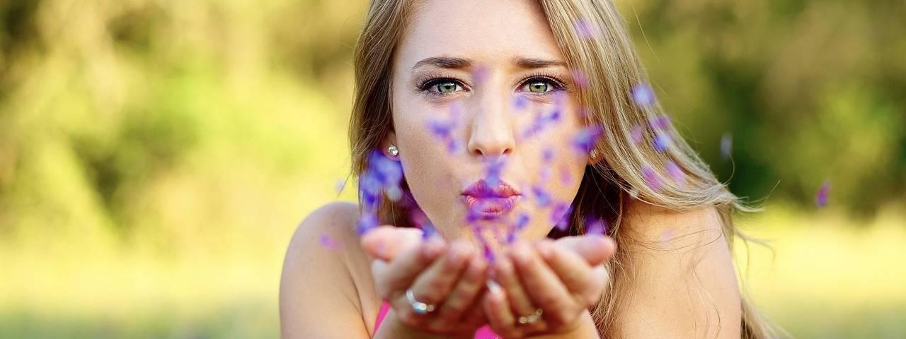 Eye care, woman with eye allergies blowing flowers in Braselton & Oakwood, Georgia