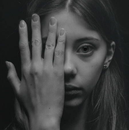 grayscale photo of woman covering her face by her hand