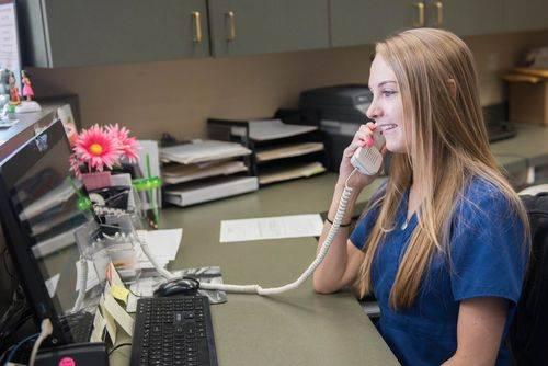 Megan J assisting patient on phone