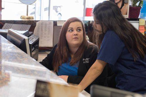Bethany and Anna working together at the front desk