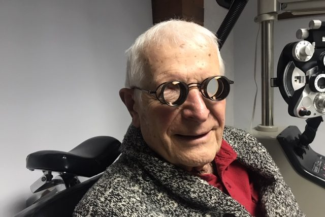 Senior man wearing low vision glasses