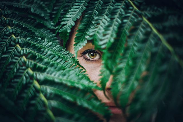 optometrist, woman showing single green eye through leaves in Laguna Beach, California