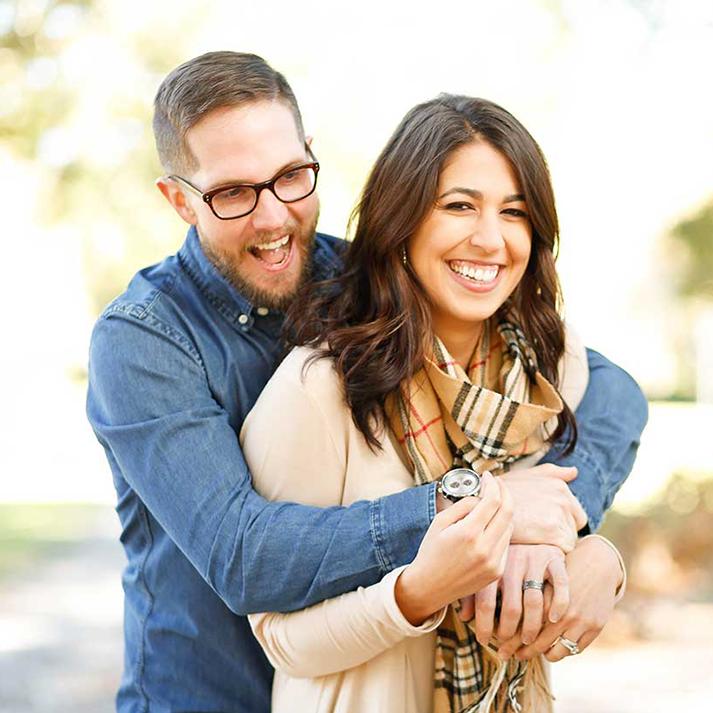 Man in eyeglasses, hugging girlfriend