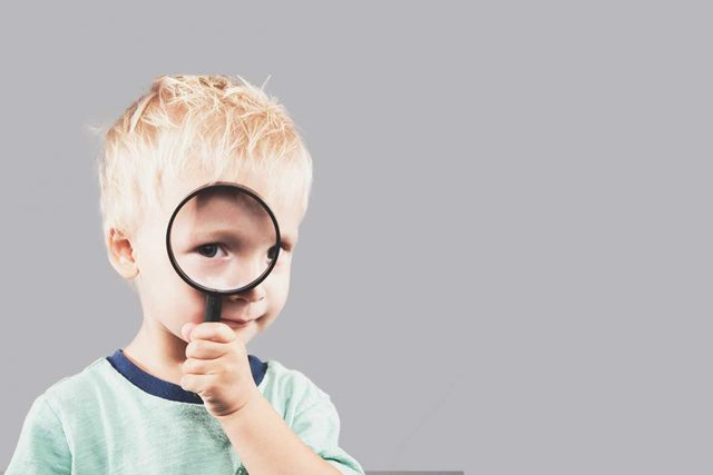 boy with magnifying glass for vision therapy