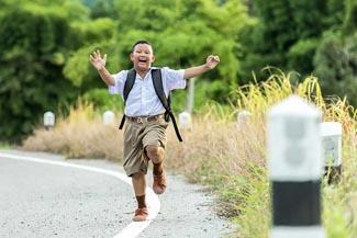 little boy skipping on road