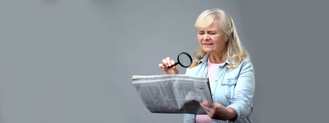 senior with magnifiying glass reading paper 1280×480