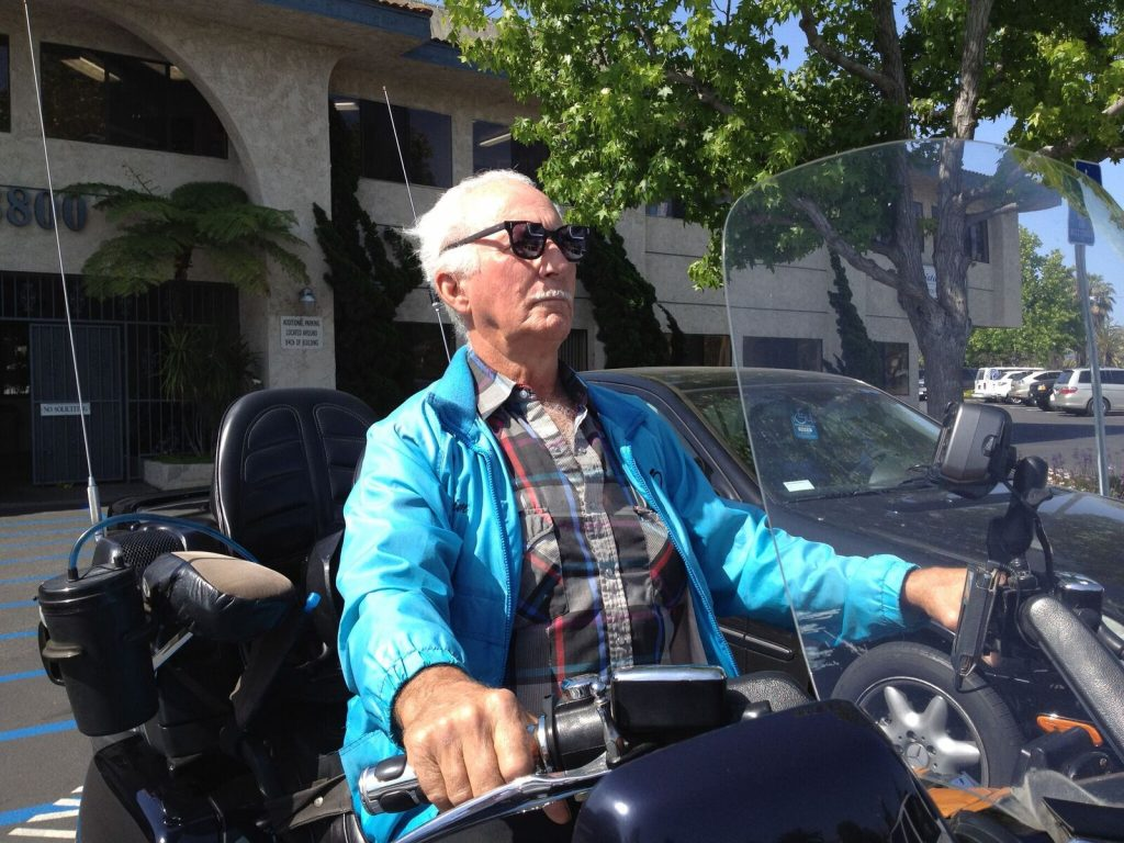 senior man riding motorcycle with low vision aids