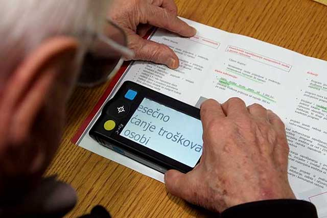 Person using electronic Low Vision Aid to read