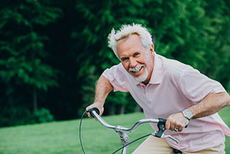 optometrist, Lively Older Man Riding His Bicycle, Laughs And Enjoys Life in Roselle, IL