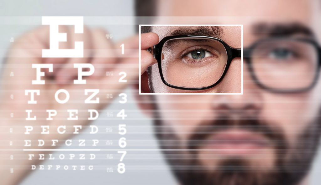 Man wearing eyeglasses, with eye chart next to him