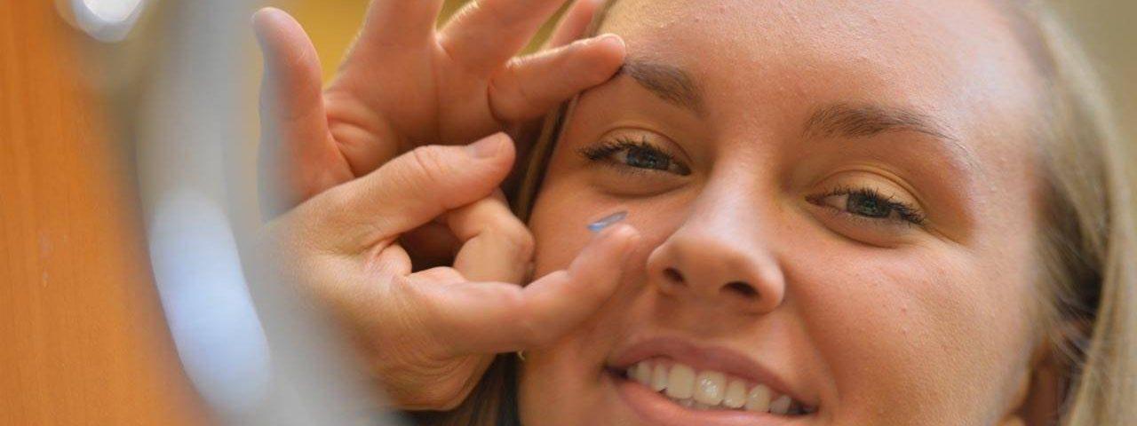Eye doctor, girl wearing contact lenses in North Miami Beach, Florida