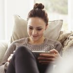 Women relaxing on couch with tablet pc