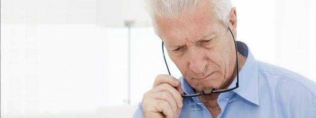Eye doctor, senior man holding eyeglasses in Holt, MI