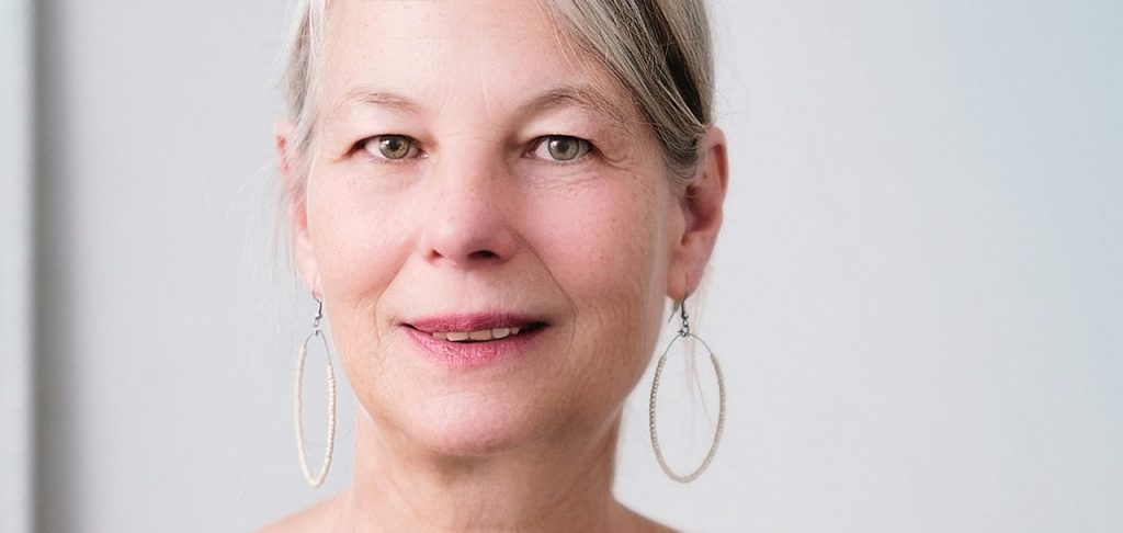 older woman with hoop earings, wearing scleral lenses