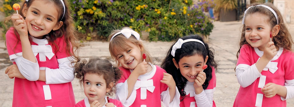 group of girls in pink with lollipops slide