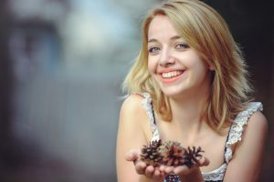 Blonde haired woman holding pine cones in Redondo Beach, California