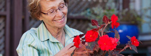 Optometrist, senior woman looking at a bouquet of flowers in San Antonio, TX