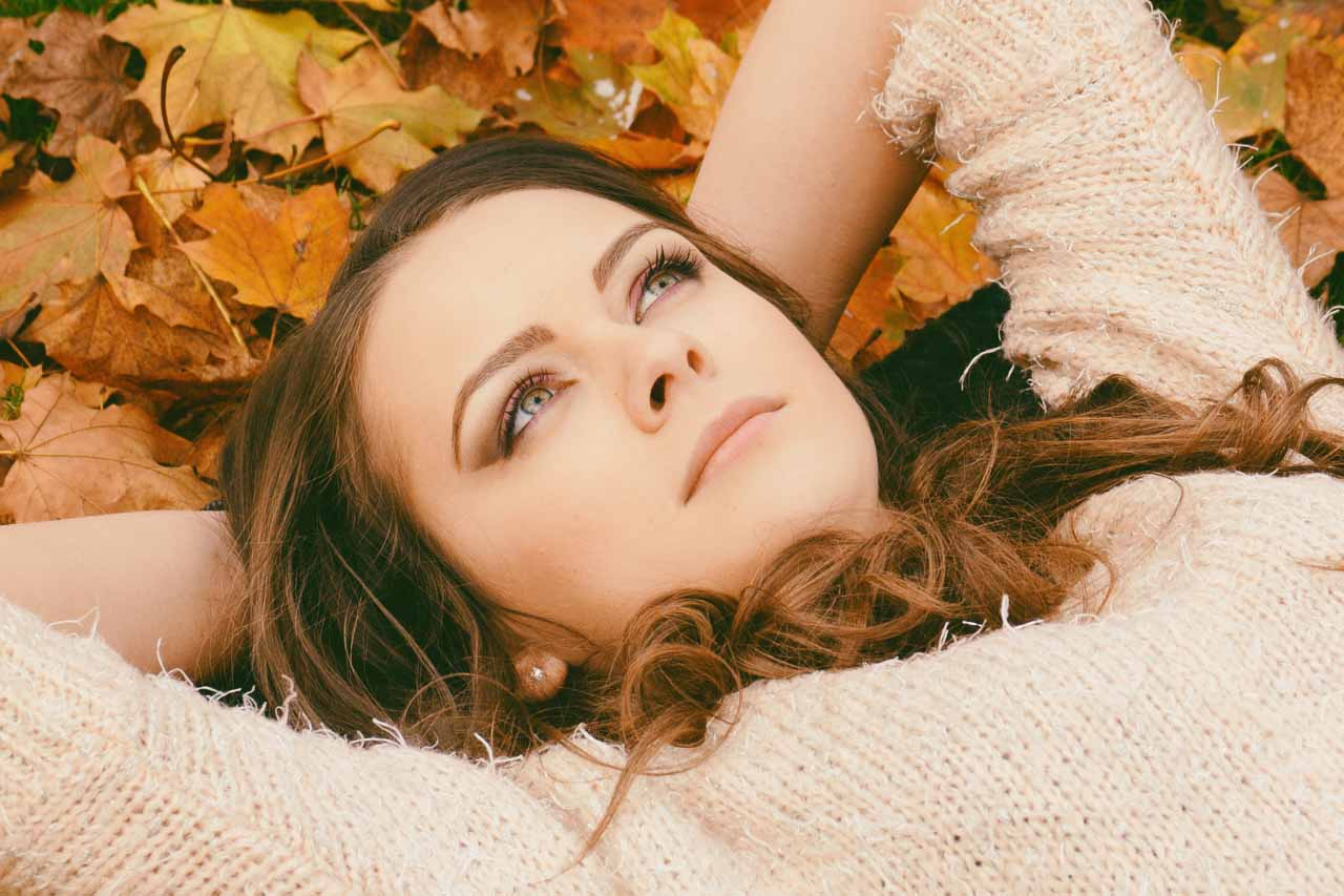 Woman with dry eye, laying in pile of leaves