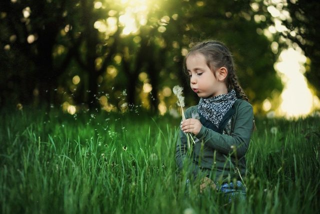 girl in the grass, wearing scleral lens