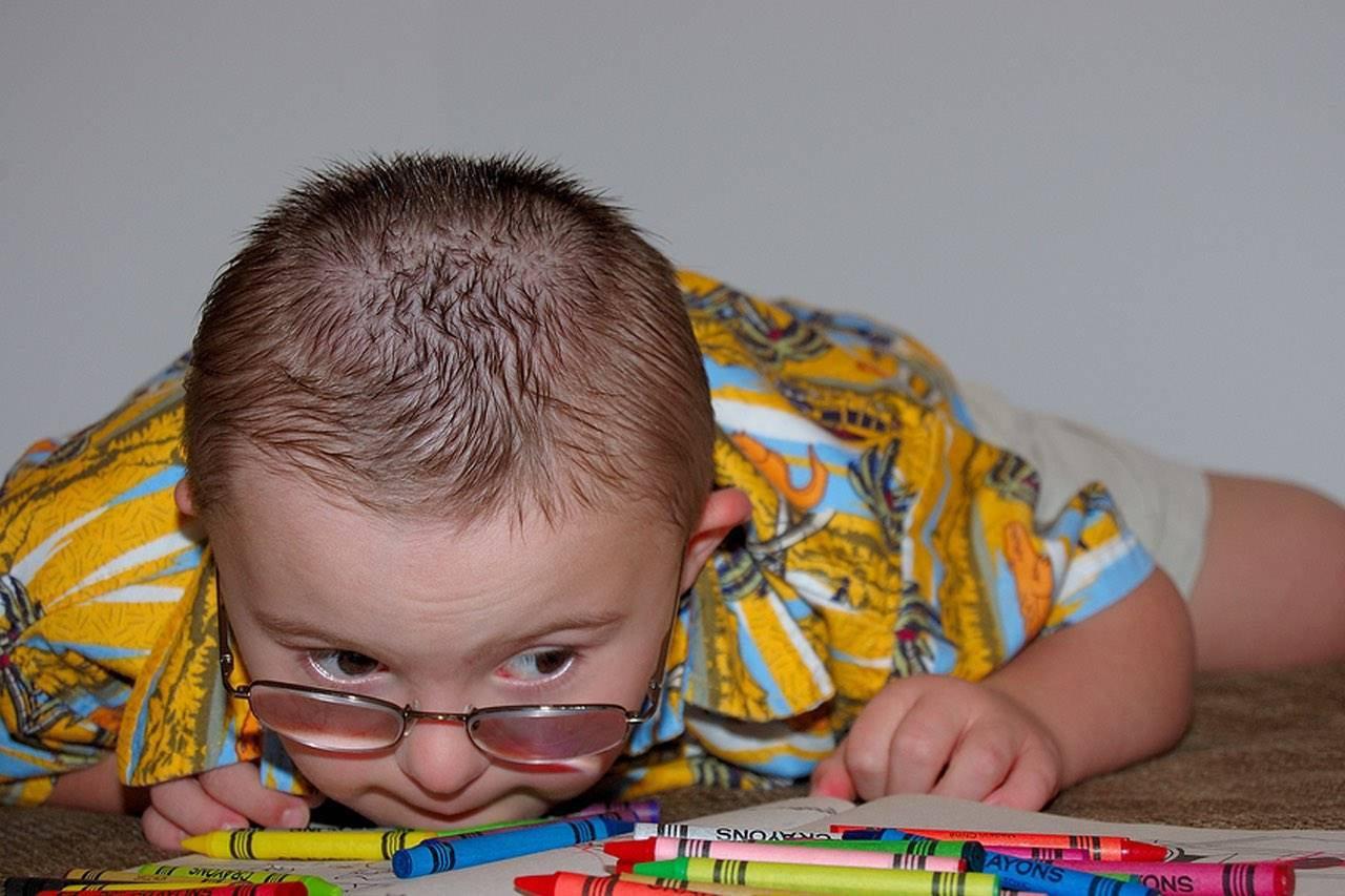 Eye doctor, special needs boy with crayons in Spring, CO