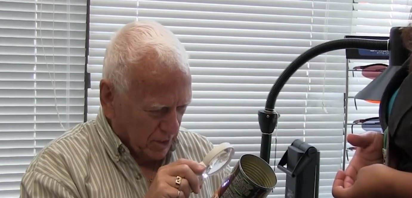 Man using handheld magnifier for low vision