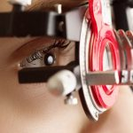 Optometrist giving eye exam to boy in Ogden, UT