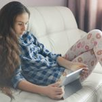 Teenage Girl Sitting On The Couch At Home Using Tablet Pc. Lifes