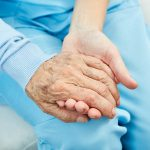 Nursing or caring nurse holds a seniors hand as a consolation