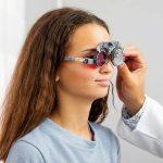 Doctor holding special eye equipment examinating girls eyes