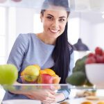 Smiling woman taking a fresh fruit out of the fridge, healthy fo