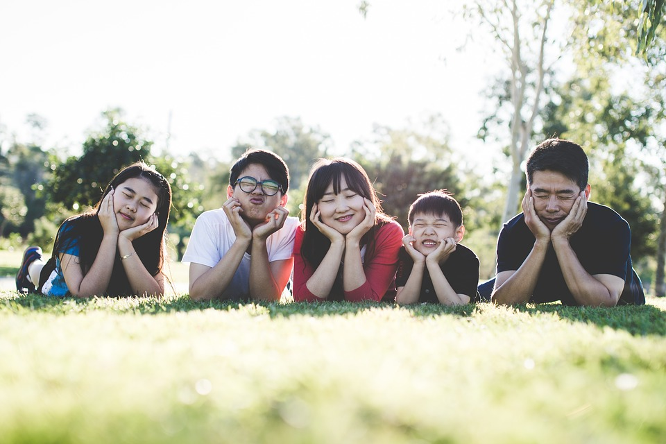 asian family sitting on the grass