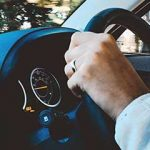 Person with Retinitis Pigmentosa holding steering wheel of car