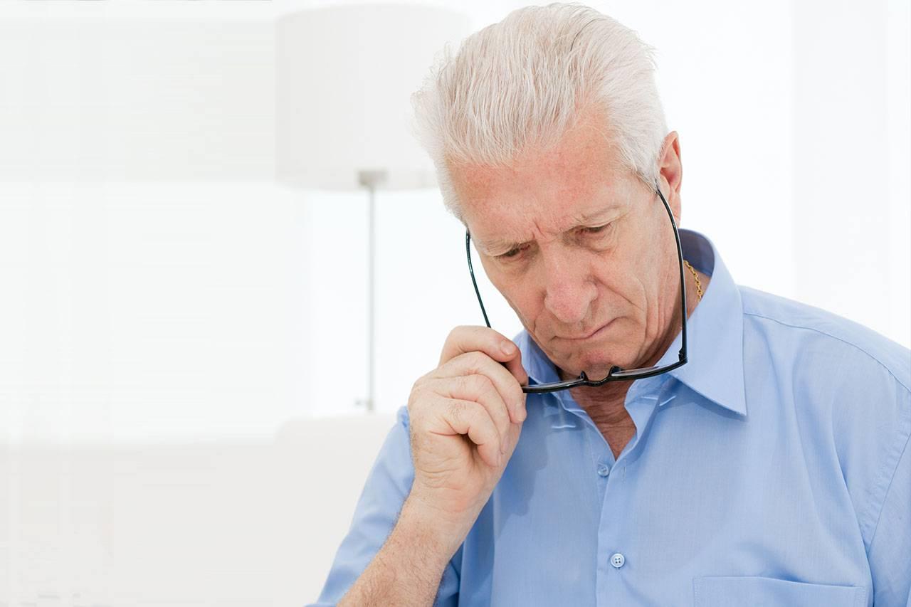 Elderly man having difficulty reading