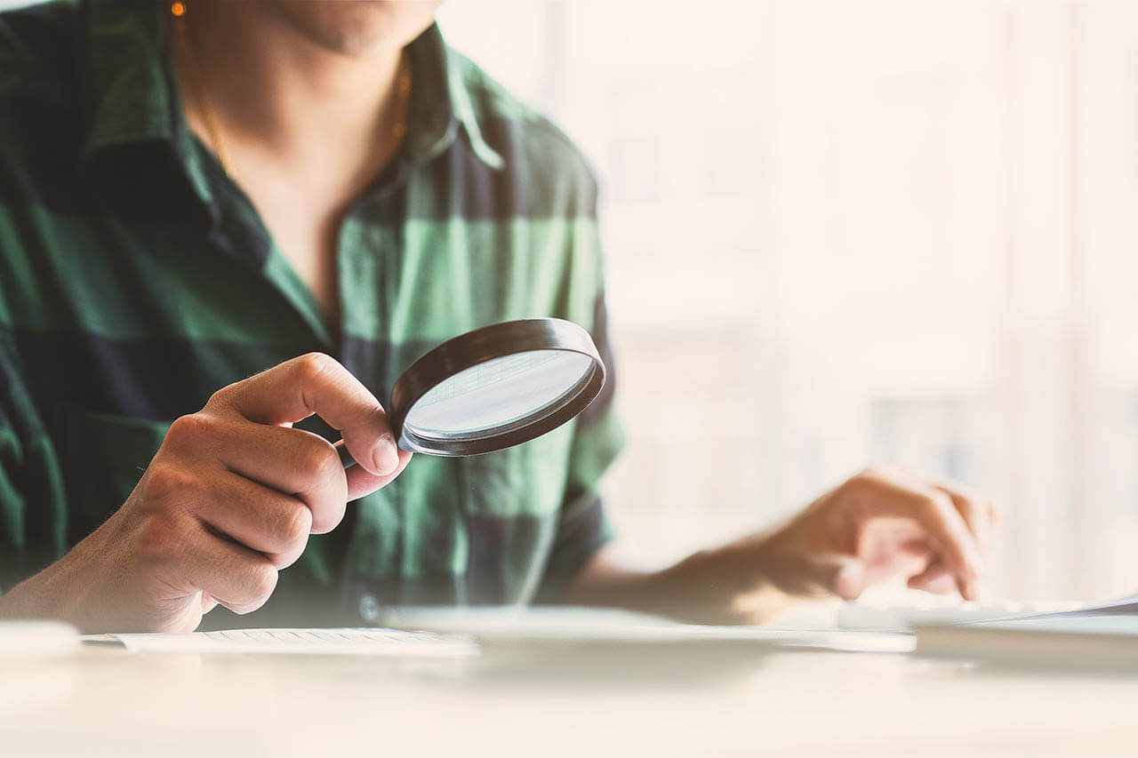 Businessman Looking Through A Magnifying Glass To Documents. Bus