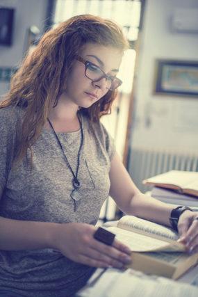 College girl reading homework efficiently