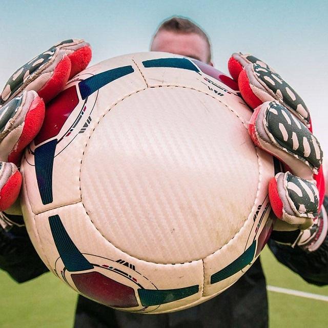gloved hands holding soccer ball