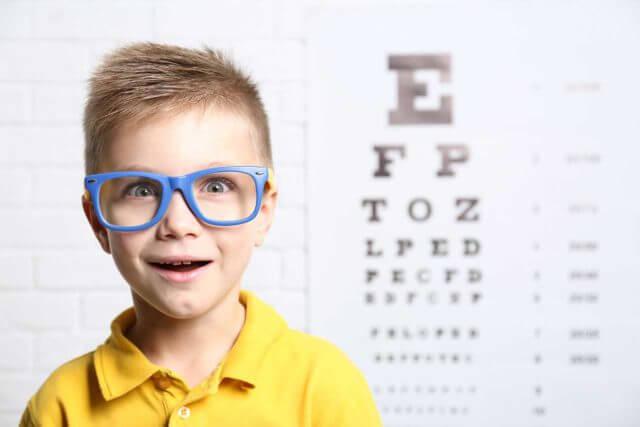 little boy with eyeglasses in his school eye exam