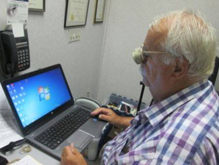 Man using computer with low vision assistance device