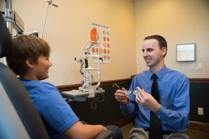 Dr. Hite fitting a boy with eyeglasses