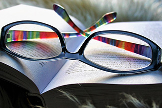 Eye care, eye glasses with scratch lenses on the book in Commerce City, CO