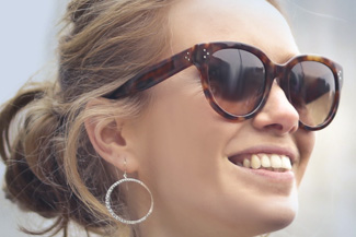 Eye exam, young woman smiling with designer frame sunglasses in Commerce City, CO