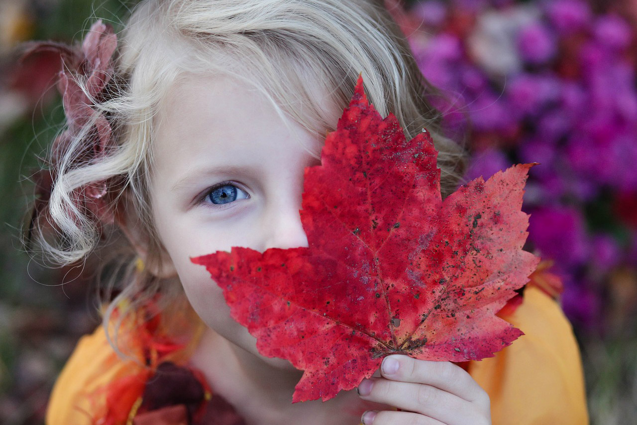 girl with autumn red maple leaf over eye