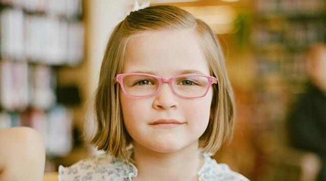 little girl wearing pink eyeglasses 640