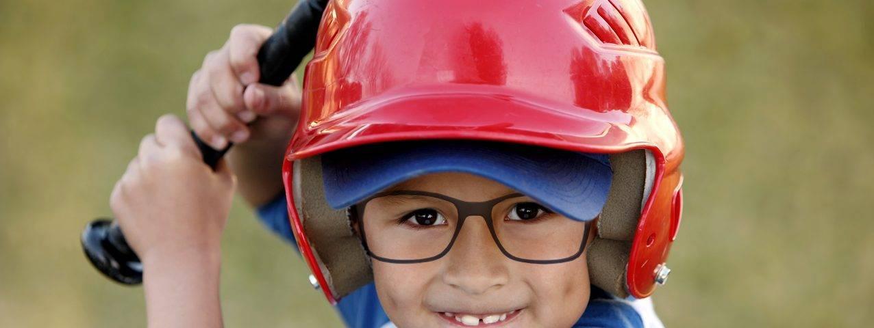 Cute little boy wearing glasses, playing baseball