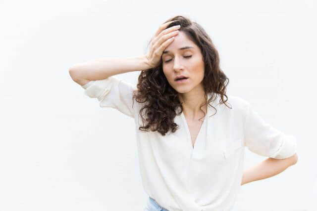 Exhausted tired woman with closed eyes touching head