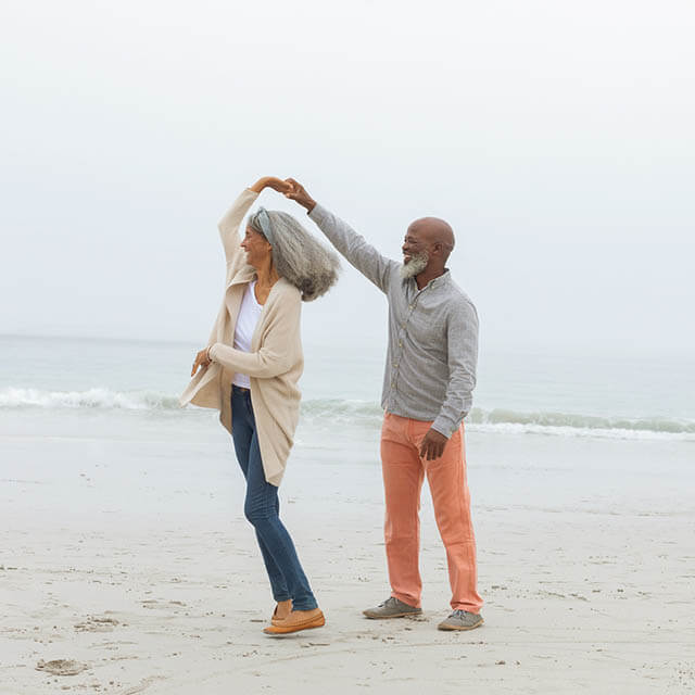 Front view of happy senior diverse Couple smiling at the beach.