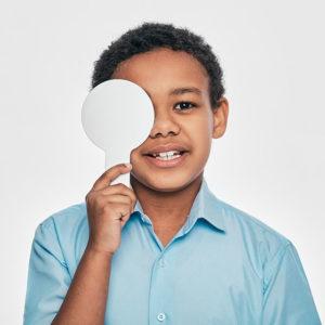 African American Male Kid Having Eye Exam With One Eye Covering